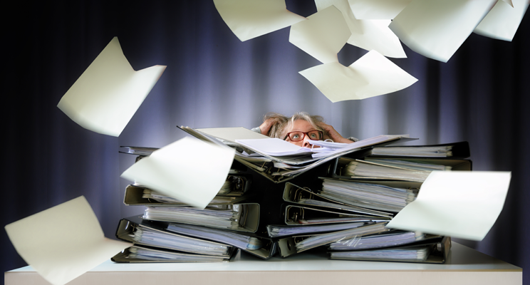 A woman behind a stack of books and paper work, which look like they have been blown into the air.